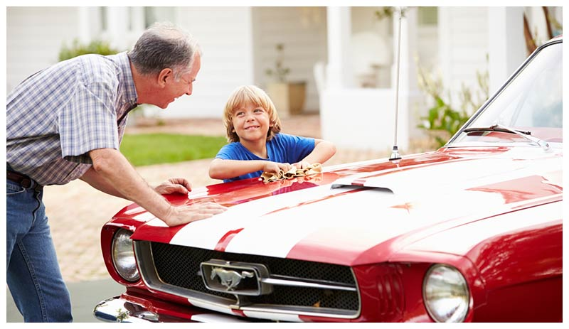 Man and child, cleaning a classic car