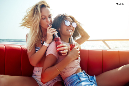 two young female friends laughing and having drinks while sitting arm in arm together on a boat on the open ocean during summer vacation-img-blog
