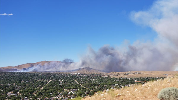 Smoke from a wildfire in a valley near homes