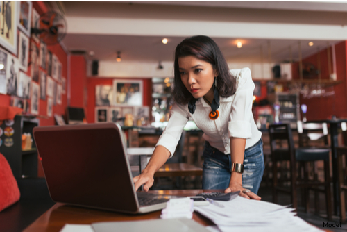 A business owner of a bar reviews her workers compensation insurance.