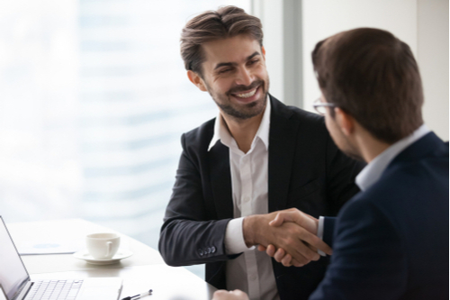 Satisfied happy businessman in suit handshake business partner