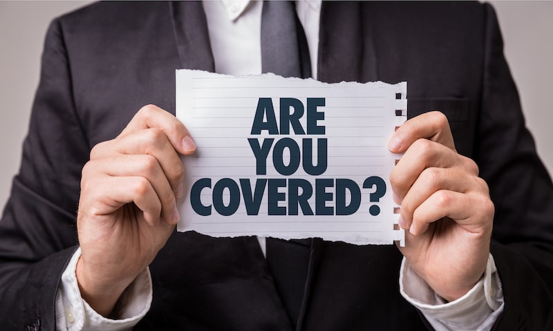 Man in a business suit holding a sign saying, 'Are You Covered.' Insurance concept