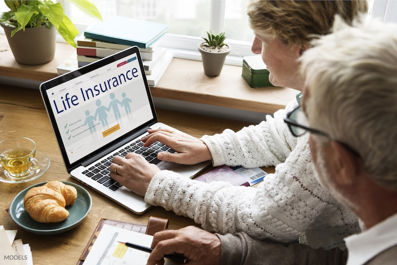 Elderly couple searching for life insurance policies on their computer.