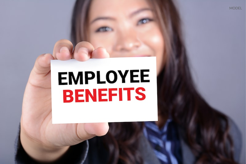 Business woman holding a card that reads employee benefits against a gray background.