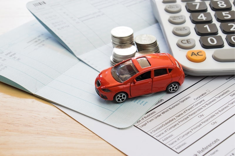 Toy car sitting on top of papers and near coins and calculator